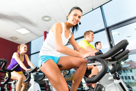 spinning: Young People - group of women and men - doing sport Spinning in the gym for fitness