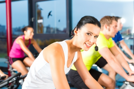 Young People - group of women and men - doing sport Spinning in the gym for fitness photo