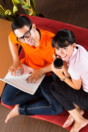 intimately: Indonesian couple sitting home on sofa with laptop using the internet for email and online shopping Stock Photo