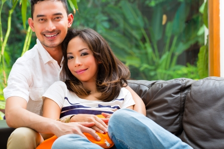 Young Indonesian couple - man and woman - sitting at home on a couch, it's weekend and they enjoying the leisure time photo