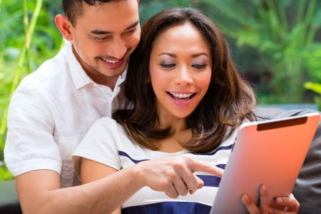 Young Indonesian couple - man and woman - sitting with a tablet computer on a couch photo