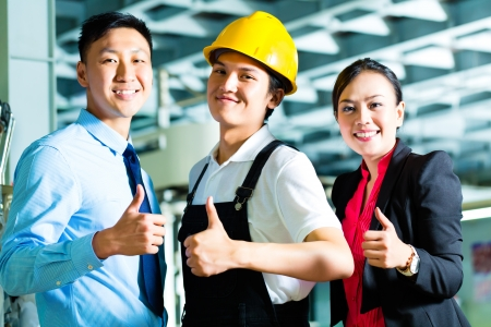 Shift supervisor or foreman, together with the owner or CEO and the Manager, standing proud in a factory photo