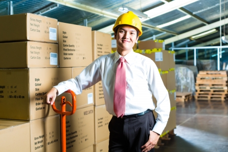 quickly: Young man in a suit standing besides boxes and packages in a warehouse