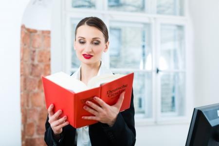 diligente: Abogado de sexo femenino joven que trabaja en su oficina de la lectura en un libro de leyes t?pica