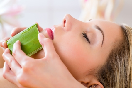 face massage: Wellness - woman receiving head or face massage whit aloe Vera in spa Stock Photo