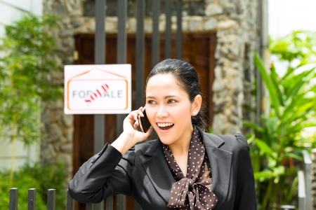 accommodation broker: Real estate - Young Indonesian realtor showing an house or apartment, it could be the landlord too, she has a customer conversation with a prospective customer on the mobile phone Stock Photo