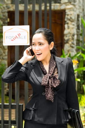 landlord: Real estate - Young Indonesian realtor showing an house or apartment, it could be the landlord too, she has a customer conversation with a prospective customer on the mobile phone Stock Photo