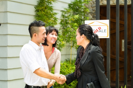 lease: Real estate market - young Indonesian couple looking for real estate apartment or house to rent or buy, the realtor and the client shaking hands