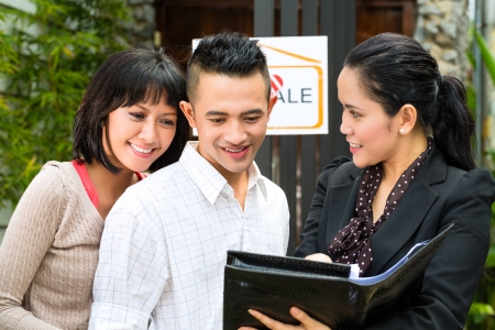 Real estate market - young Indonesian couple looking for real estate apartment or house to rent or buy, the realtor showing a document photo