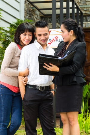 Real estate market - young Indonesian couple looking for real estate apartment or house to rent or buy, the realtor showing a document Stock Photo - 20180212