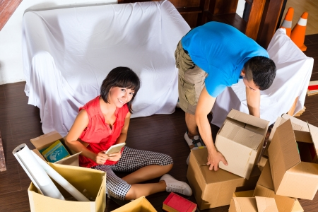 shipper: Real estate market - Young Indonesian couple moving in a home or apartment, they unpacking moving boxes