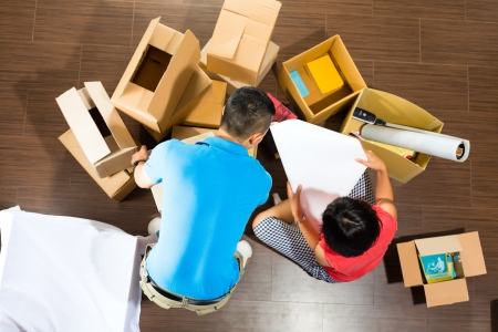 apartment market: Real estate market - Young Indonesian couple moving in a home or apartment, they unpacking moving boxes