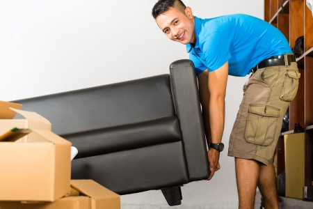 Real estate market - Young Indonesian man lifting a sofa put it away photo
