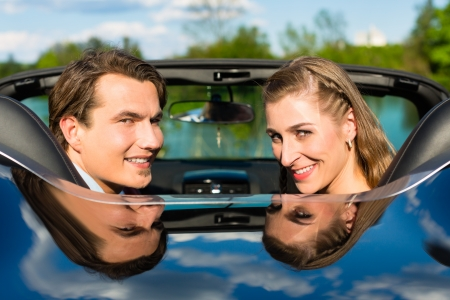 Young hip couple - man and woman - with cabriolet convertible car in summer on a day trip photo