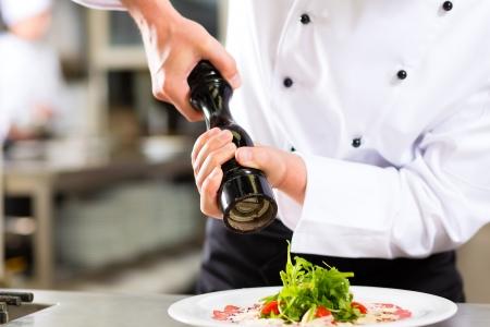ホテルまたはレストランの台所の調理でシェフだけ見られる、彼は料理を調味料に手します。 写真素材 - 20112809
