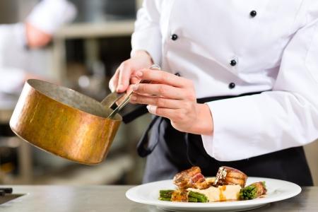 chef cocinando: Female Chef en el hotel o restaurante cocina cocina, s�lo las manos para ser visto, se est� trabajando en la salsa de la comida, ya saucier