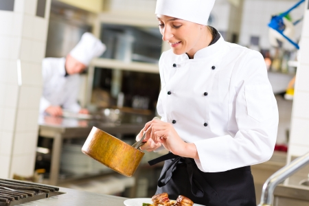 Female Chef in hotel or restaurant kitchen cooking, she is working on the sauce as saucier Stock Photo - 20180003