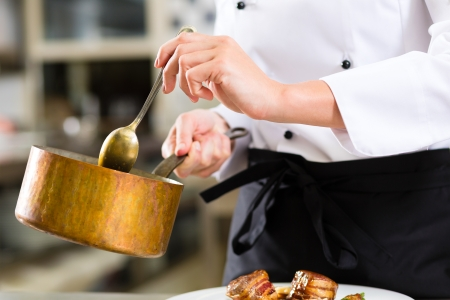 Female Chef in hotel or restaurant kitchen cooking, only hands to be seen, she is working on the sauce as saucier Stock Photo - 20180008