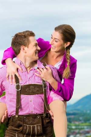 Happy Couple in traditional dress is standing in the meadow with mountain panorama photo