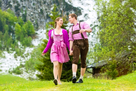 enyoing: Happy Couple in traditional dress is walking in the meadow with mountain panorama