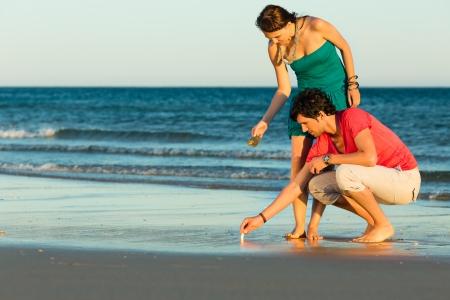 románský: Muž a žena, pár, se těší na romantický západ slunce na pláži u moře v jejich dovolené, ale vyhledávání skořápky
