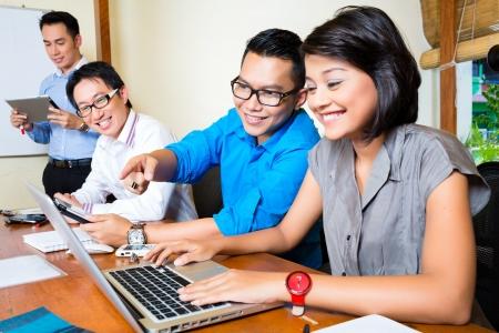 Aziatische Creative agency - team bijeenkomst in een kantoor met laptop
