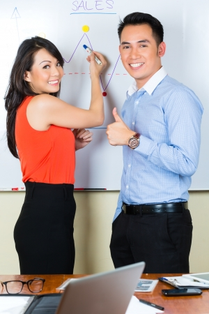 Asian Creative agency - Two colleagues showing the development of sales with a diagram on a whiteboard photo