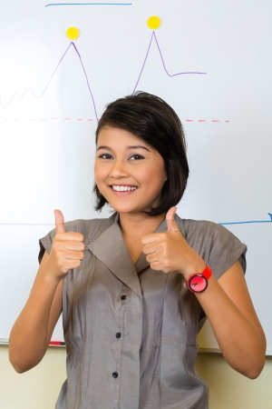 Asian Creative agency - businesswoman showing the development of sales with a diagram on a whiteboard, thumbs up photo