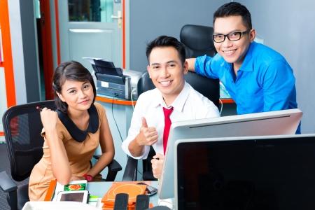 indonesian woman: Agencia creativa Asi�tico - reuni�n del equipo en una oficina con ordenador port�til