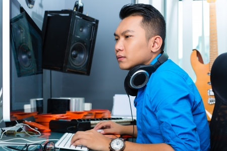 music production: Asian musician, producer or mixer in sound studio