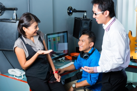 production: Asian people, musician, producer and mixer in sound studio