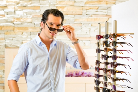 Young man at optician with glasses, he might be customer or salesperson and is looking for sunglasses photo