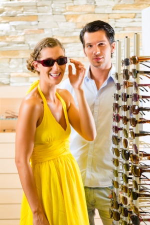 Young woman at optician with glasses, they are looking for sunglasses photo