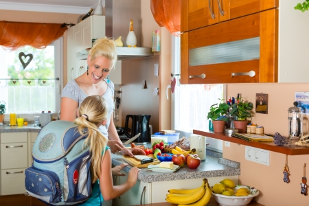 backpack school: Family - mother making breakfast for her children in the morning and a snack for school
