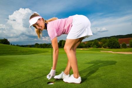 Junge weibliche Golfer auf Kurs zu tun Golfschwung, sie vermutlich aus?bt,