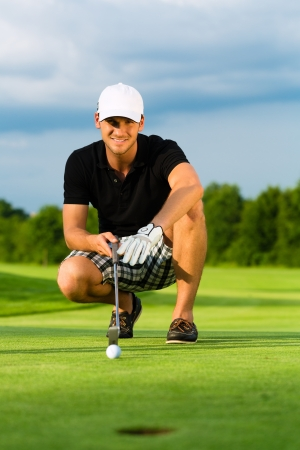 golf glove: Young golf player on course putting, he aiming for his put shot