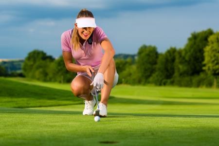 lanzamiento de bala: Jugador de golf femenino joven en curso con el objetivo de poner