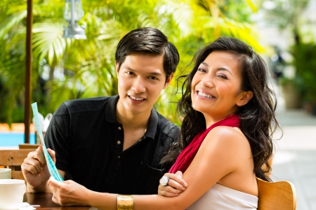 Asian man and woman in restaurant are selecting the food and are hungry photo