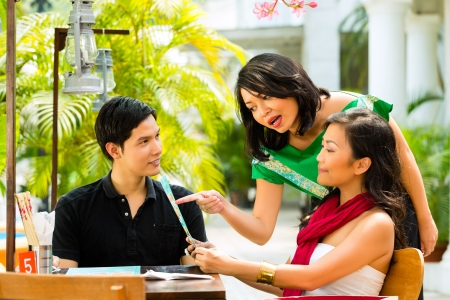 recommendation: Asian man and woman in restaurant, waitress is recommending a dish Stock Photo