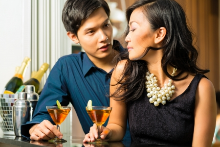seducer: Asian man and woman in flirting intimately at bar drinking cocktails Stock Photo