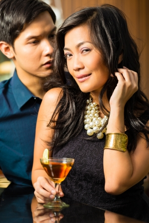 Asian man and woman in flirting intimately at bar drinking cocktails photo