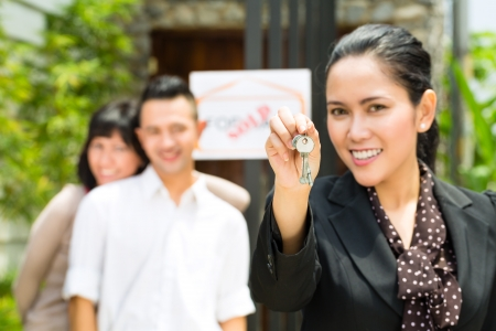accommodation broker: Real estate market - young Indonesian couple looking for real estate apartment or house to rent or buy, the realtor holding the keys