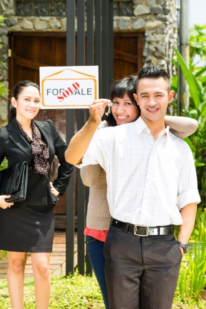 Real estate market - young Indonesian couple looking for real estate apartment or house to rent or buy, the woman holding the keys photo