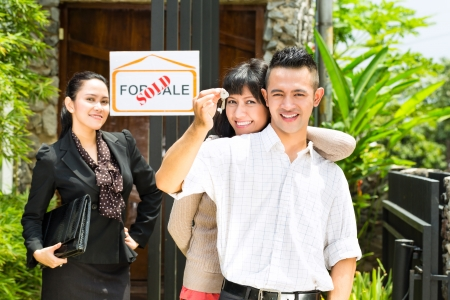 accommodation broker: Real estate market - young Indonesian couple looking for real estate apartment or house to rent or buy, the woman holding the keys Stock Photo