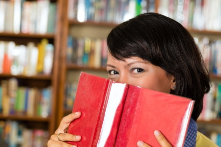 Student - young Asian woman or girl learning in library and reading, she hides behind a book photo