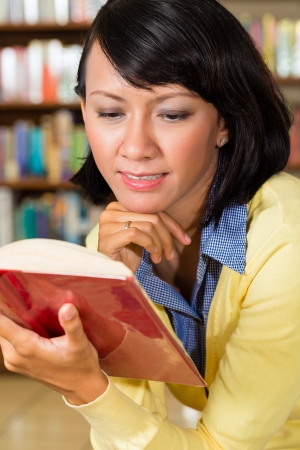 Student - a young Asian woman or girl learning in a library reading a book Stock Photo - 20757254