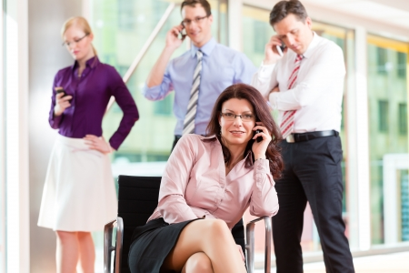 Business people - female boss and employees in office, all making a call with their mobiles photo