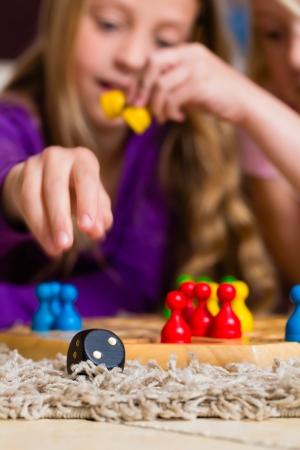 Familia - dos hermanas - jugar juego de mesa parch?s en casa en el suelo, se centran en los dados en la parte delantera