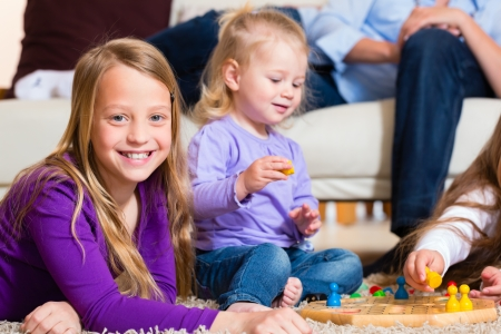 board games: Family playing board game ludo at home on the floor Stock Photo
