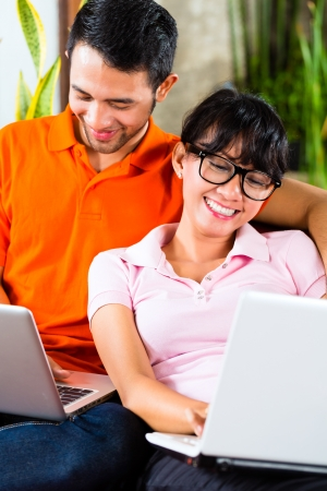 Young Indonesian couple - man and woman - sitting with laptops on a couch photo